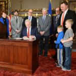 Sen. Andrew Lang (R-Olivia) and his two children, right, watch as Gov. Mark Dayton signs his $35 million Rural Finance Authority legislation into law